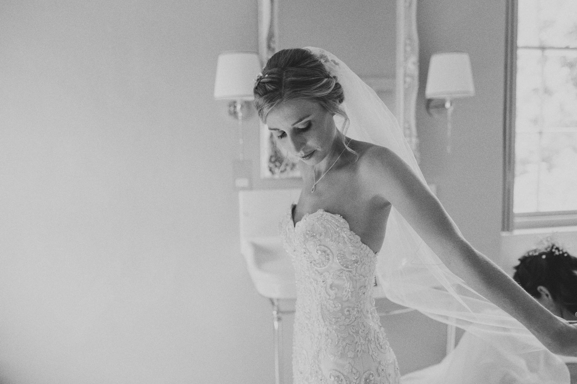 black and white shot of bride putting on wedding dress