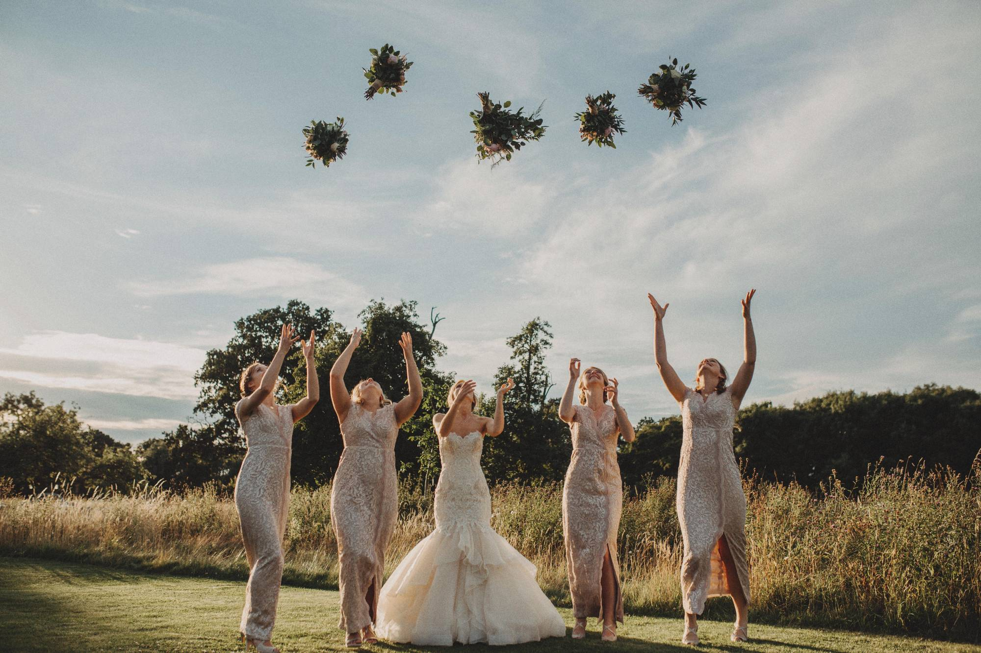 bridesmaids throwing flowers in the air
