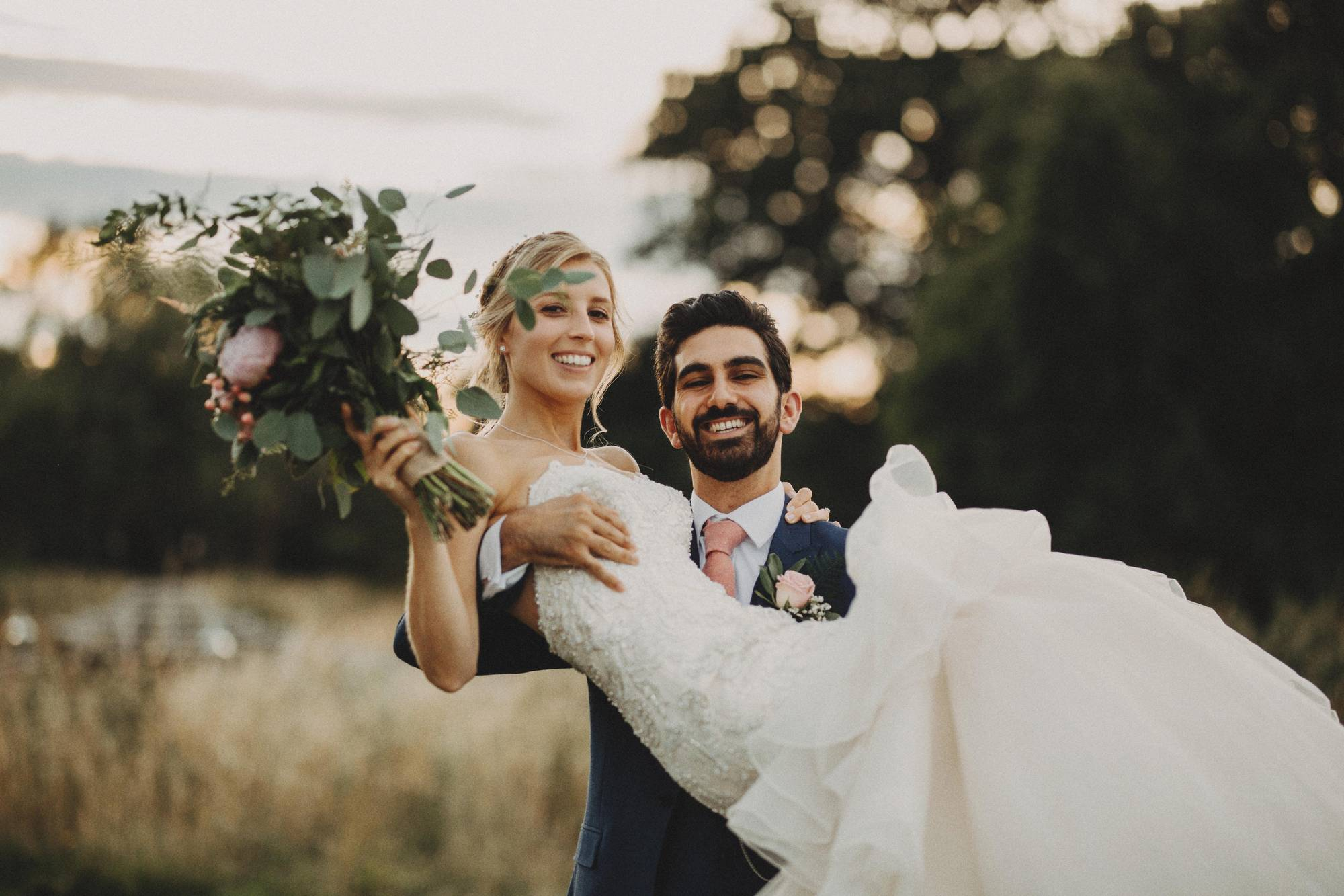 Groom carries bride in arms at elmore court wedding